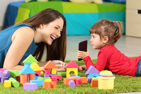 Toddler showing a smart phone to her mother lying on a carpet in a room