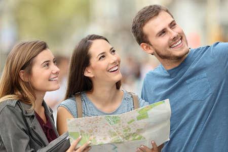 거리에 서있는 휴가를 즐기는지도를 들고 세 행복 관광객 스톡 콘텐츠