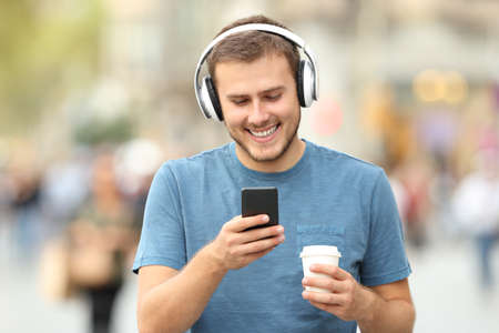 Front view of a happy man walking listening to music wearing headphones and holding a take away drink on the street