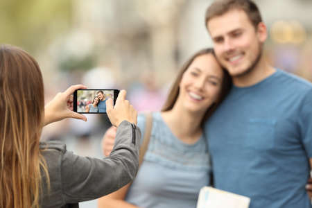 Three happy friends taking photos with a smart phone outside on the street Reklamní fotografie