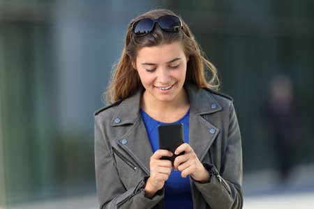 Front view portrait of a happy girl using a smart phone walking outdoors on the street