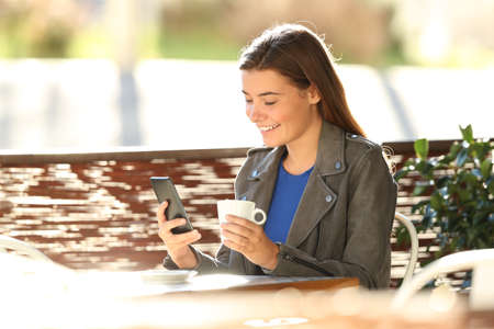 Single fashion teen using a smart phone sitting in a coffee shop terrace with a back light in the background Reklamní fotografie