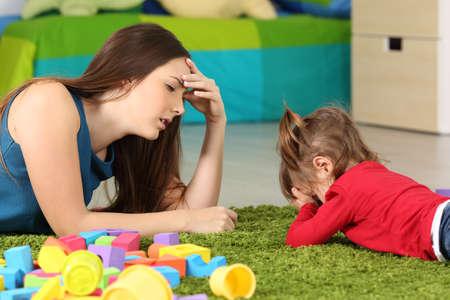 Bambino arrabbiato e madre stanca sdraiata su un tappeto in una stanza
