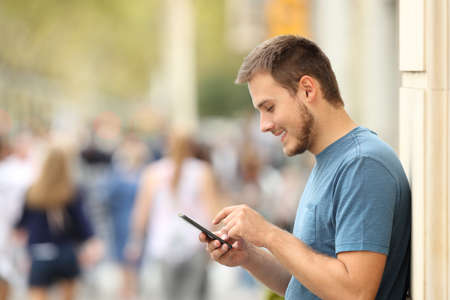 Side view of a happy guy texting on a smart phone leaning on a wall on the street