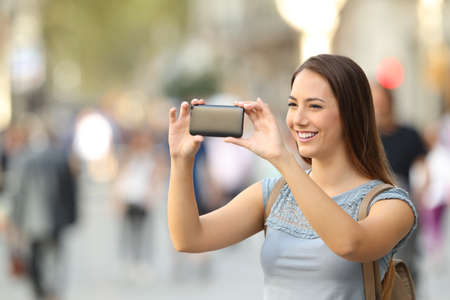 Single happy woman taking photos with a smart phone on the street