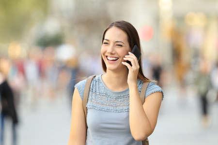 Gelukkige vrouw die een mobiele telefoon uitnodigt die op de straat loopt Stockfoto