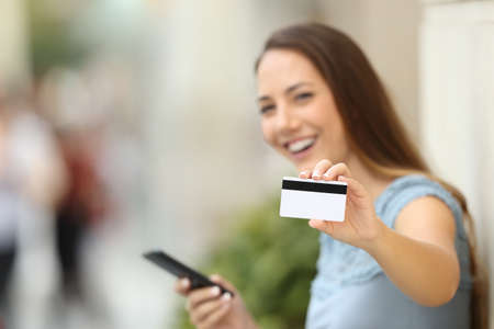 Happy on line buyer showing a credit card to the camera on the street Reklamní fotografie
