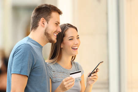 Couple buying on line with a credit card and a smart phone watching a storefront outdoors on the street Фото со стока