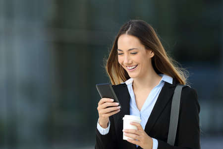 Single executive checking content in a smart phone and holding a take away coffee walking on the street