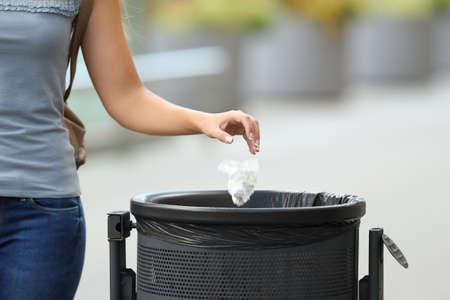 Schließen Sie oben von einem werfenden Abfall der bürgerlichen Frauenhand in einem Abfalleimer auf der Straße Standard-Bild
