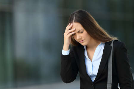 Single executive suffering headache walking outside on the street