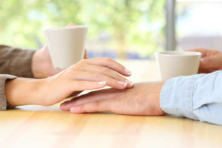 Close up of a couple dating and touching hands in a bar or house