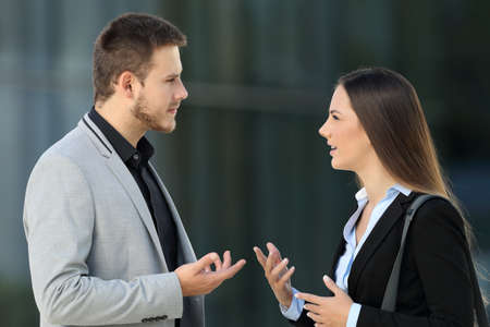 Side view portrait of two executives talking seriously standing outdoors on the street Stock Photo