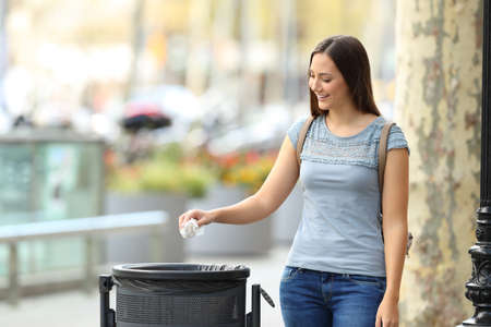 Single civic woman throwing a paper into a trash bin on a city street