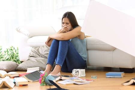 Sad homeowner lamenting after robbery sitting on the floor of the living room at home