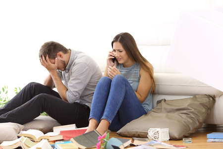 Desperate couple calling police after a robbery sitting on the floor of a messy living room at home