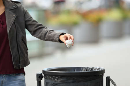 Close up of a lady hand throwing garbage to a trash bin on the street Archivio Fotografico