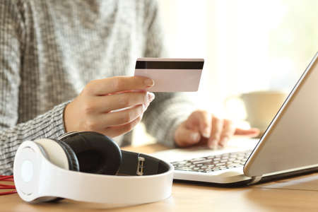 Close up of an on line buyer hands buying music with a laptop and credit card at home