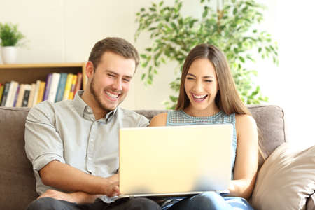 Couple laughing watching on line content in a laptop sitting on a sofa at home