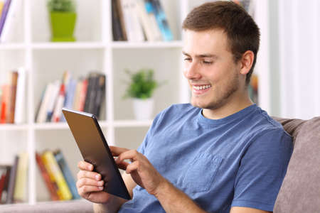 e book device: Happy man using a tablet sitting on a sofa at home Stock Photo