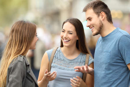 Portrait of three smiling friends talking together standing on the street Banco de Imagens