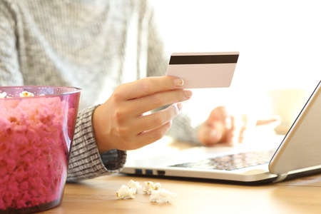 Close up of a woman hand buying pay per view movies on line with credit card and a laptop on a table at home Stock Photo