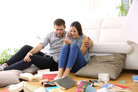 Sad couple calling to police sitting on the floor of the messy living room after home robbery Foto de archivo