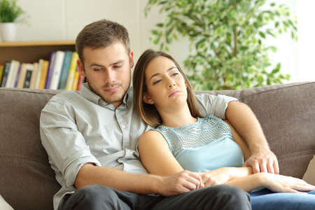 Bored couple wasting time sitting on a sofa at home