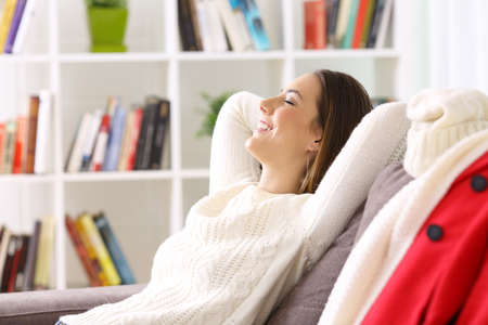 Side view of a woman relaxing sitting on a sofa when she gets home in winter Stock Photo