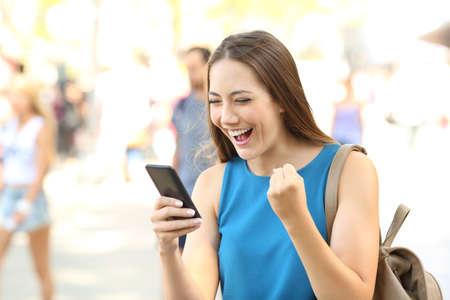 femme excitée lisant des nouvelles sur la ligne dans un téléphone intelligent sur la rue