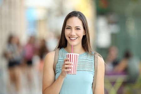 bebes lindos: Retrato frontal de una niña sosteniendo una bebida para llevar y mirando a la cámara en la calle