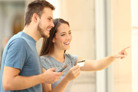 On line buyers watching a storefront holding a smart phone and a credit card on the street Stock Photo
