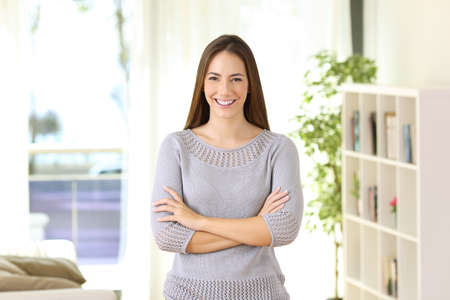 Portrait of a proud homeowner posing looking at you standing in the living room at home Stock Photo