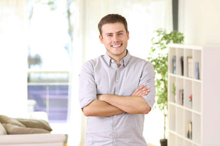 Happy homeowner portrait posing standing at home with furniture and window in the background