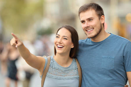 Happy couple finding location and pointing at side walking on the street