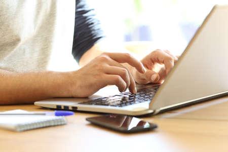 自宅で机の上にラップトップで手書きの人の手のクローズアップ