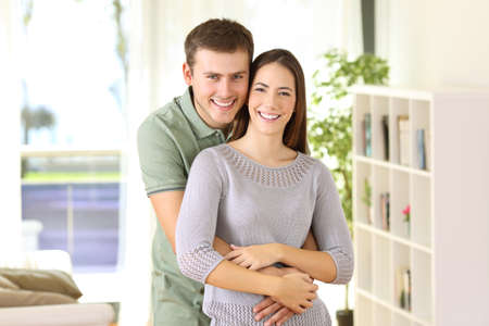 Portrait of a proud homeowners posing looking at you standing in the living room at home