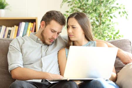 ノートパソコンと彼の動揺ガールフレンドの行の内容を見た後眠っている退屈な彼氏は自宅で彼を見て 写真素材