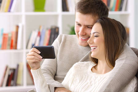 Happy couple watching on line content in a smart phone sitting on a sofa at home 免版税图像