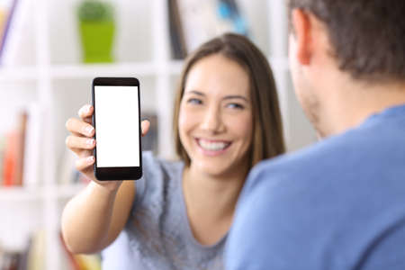 Woman showing a smart phone screen to a friend at home Imagens