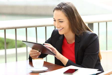 바 테라스에 앉아 타블렛을 사용하는 라인에서 일하는 한 명의 임원