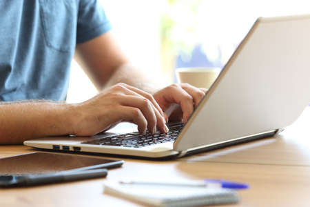 Close up of man hands typing on a laptop keyboard on a desk at home or office