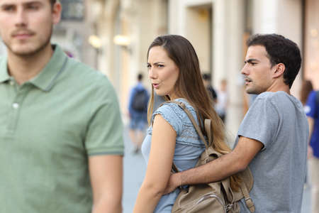 Disloyal woman looking another man and her angry boyfriend looking at her on the street