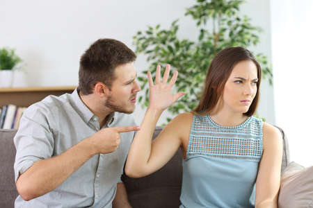 Angry couple fighting sitting on a couch at home