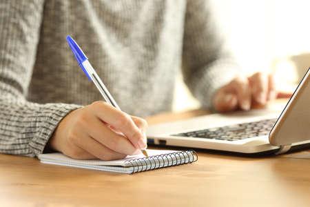 Cerca de las manos de una mujer tomando notas en un cuaderno y una computadora portátil en un escritorio en casa en invierno