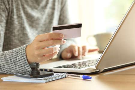 Cerca de una mano de mujer pagando en línea con tarjeta de crédito y una computadora portátil en un escritorio en casa Foto de archivo - 88328307