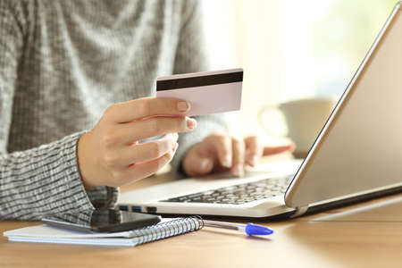 Close up of a woman hand paying on line with credit card and a laptop on a desktop at home