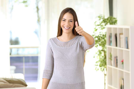 inversion: Front view portrait of a satisfied home owner looking at camera standing in a house interior Stock Photo