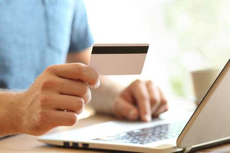 Close-up de uma mão de homem pagando on-line com cartão de crédito e um laptop em um desktop em casa