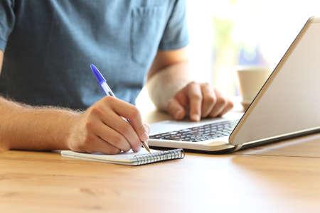 Schließen Sie oben von einer Mannhand auf der Linie, die Kenntnisse in einem Notizbuch und in einem Laptop auf einem Standard-Bild